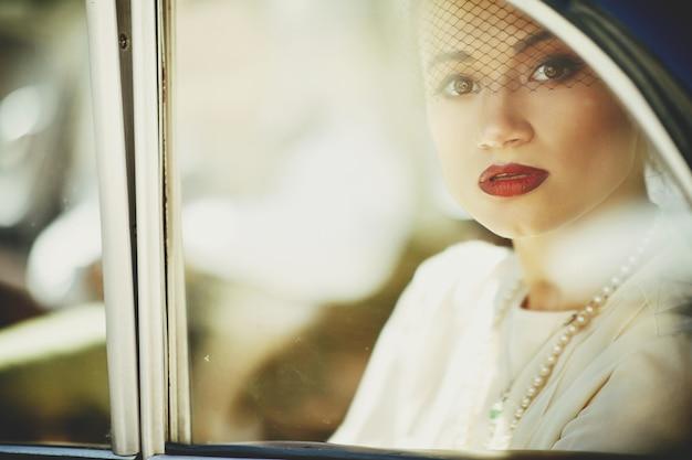 Superbe femme mystérieuse est assis dans une voiture rétro