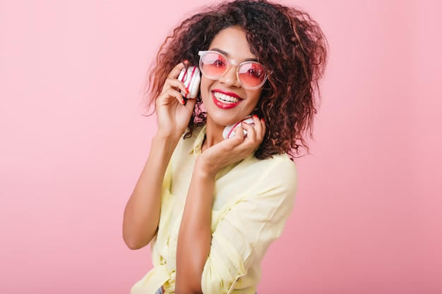 Superbe femme à la peau brillante brun clair détendue avec de la musique préférée. portrait de fille mulâtre heureuse dans des lunettes de soleil colorées à la mode, écouter de la musique dans les écouteurs.