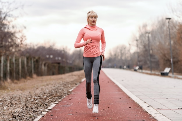 Superbe femme de race blanche blonde dédiée en tenue de sport et avec queue de cheval en cours d'exécution sur l'hippodrome.
