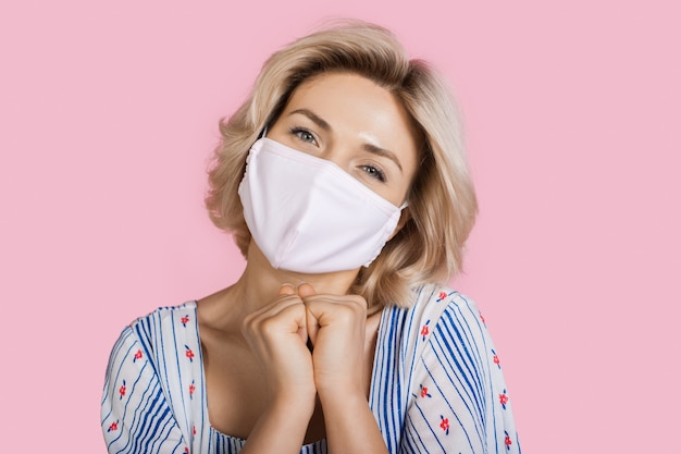 Superbe femme de race blanche faisant des gestes de plaisir sur un mur de studio rose portant un masque médical sur le visage