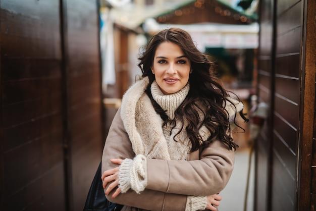 Superbe femme de race blanche en manteau debout dans la rue par temps froid avec les bras croisés.