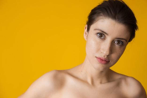Superbe femme de race blanche avec des taches de rousseur regardant à l'avant et posant sur un mur jaune avec des épaules nues