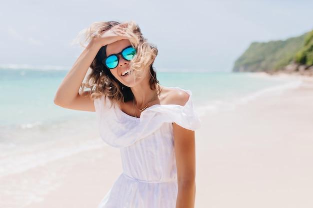 Superbe femme en robe blanche touchant ses cheveux sur la mer. femme insouciante bronzée à lunettes de soleil exprimant son bonheur pendant ses vacances.