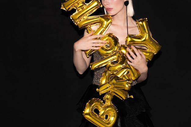 Superbe femme en robe scintillante tenant des ballons en forme de lettre tout en vous souhaitant un joyeux anniversaire à la fête sur fond noir