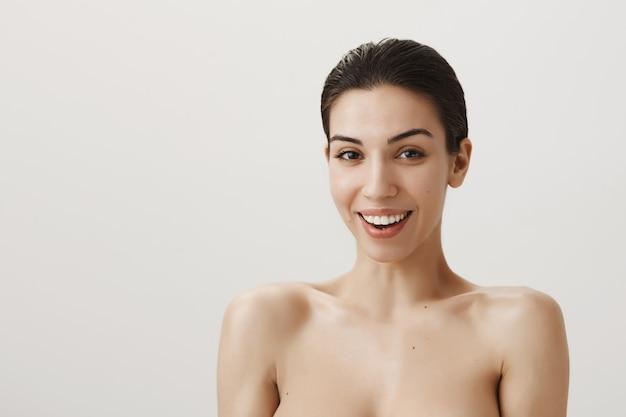 Superbe femme souriante debout nue et regardant