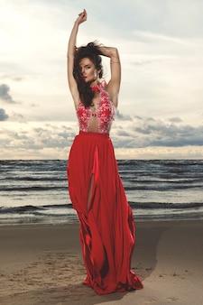 Superbe femme vêtue d'une belle robe rouge sur la plage pendant le coucher du soleil