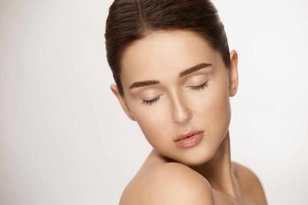 Superbe femme avec les yeux fermés et les cheveux attachés sur fond blanc