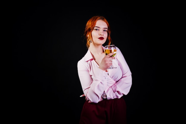 Superbe fille aux cheveux rouges en chemisier rose et jupe rouge avec verre de vin à la main, isolée sur fond noir.