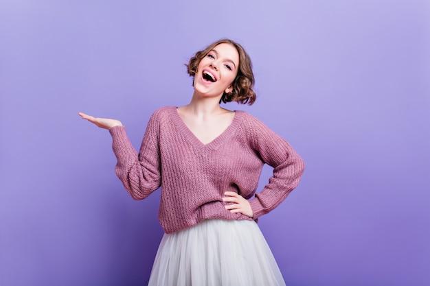 Superbe fille blanche avec une expression de visage heureux posant portrait de jolie dame caucasienne en pull et jupe luxuriante riant sur le mur violet.