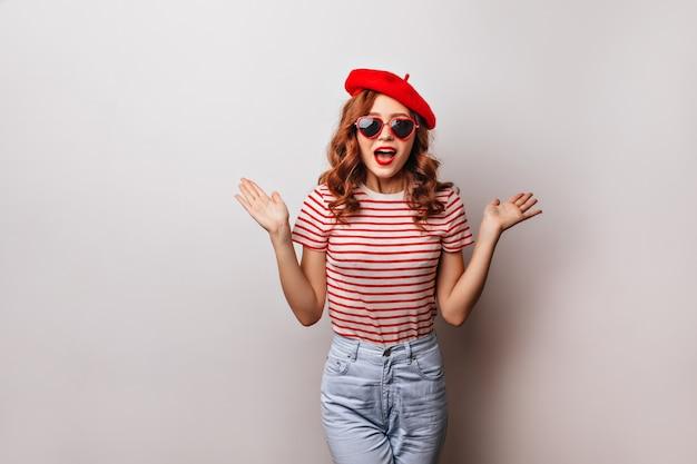 Superbe fille bouclée posant dans des lunettes de soleil à la mode. winsome modèle féminin français exprimant le bonheur.