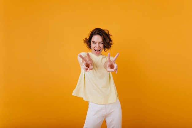 Superbe fille bouclée en t-shirt jaune danse drôle avec un sourire sincère. femme aux cheveux bruns insouciante, froid et riant.