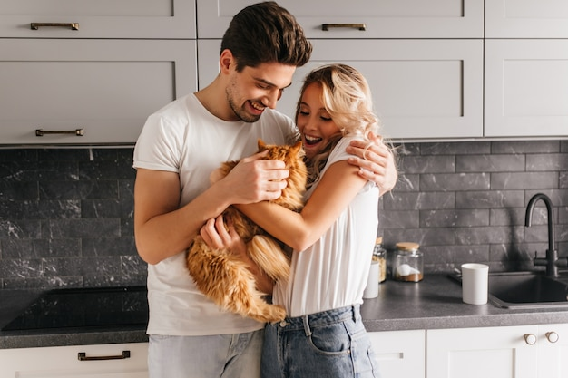 Superbe fille bouclée tenant un chat moelleux. portrait intérieur d'un couple européen jouant avec leur animal de compagnie.
