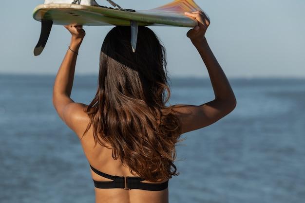 Superbe fille brune dans un soutien-gorge noir tient une planche de surf au-dessus de sa tête près de la mer vue arrière