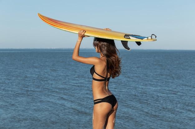 Superbe fille brune en maillot de bain noir tient une planche de surf jaune au-dessus de sa tête près de la mer par une journée ensoleillée