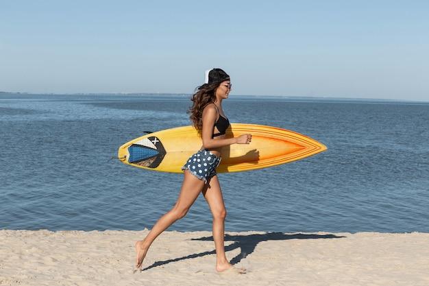 Superbe fille brune mince en lunettes de soleil et casquette vêtue d'un soutien-gorge noir et d'un short en jean court près de la mer et tient une planche de surf jaune par une journée ensoleillée. .