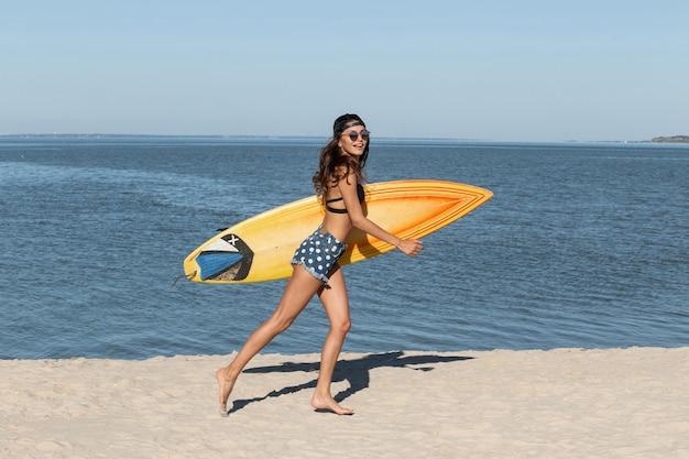 Superbe fille brune mince en lunettes de soleil et casquette vêtue d'un soutien-gorge noir et d'un short en jean est près de la mer et tient une planche de surf jaune par une journée ensoleillée. .