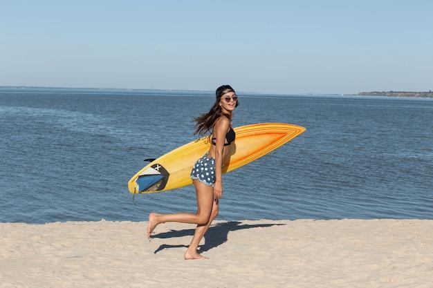 Superbe fille brune mince en lunettes de soleil et casquette vêtue d'un soutien-gorge noir et d'un short en jean s'amuse près de la mer et tient une planche de surf jaune par une journée ensoleillée. .