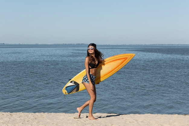 Superbe fille brune mince en lunettes de soleil et casquette vêtue d'un soutien-gorge noir et d'un short en jean se tient près de la mer et tient une planche de surf jaune par une journée ensoleillée. .