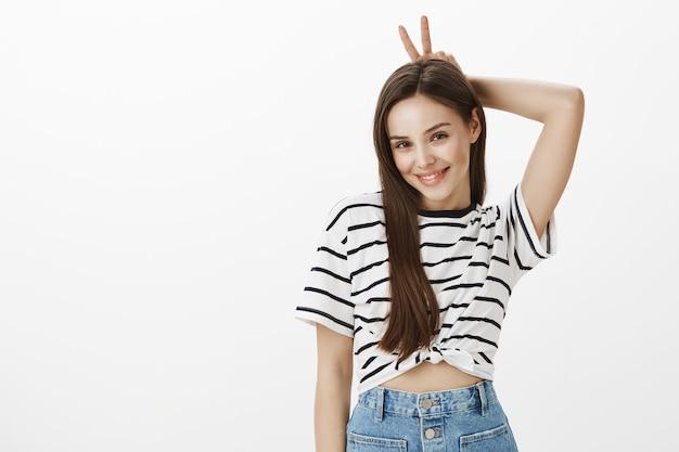 Superbe fille brune montrant le geste des cornes au-dessus de la tête, agissant de manière ludique et coquette