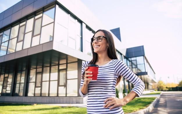 Superbe fille intelligente à lunettes se tient devant le bâtiment moderne tenant une tasse de café rouge dans sa main droite, avec sa main gauche sur une hanche