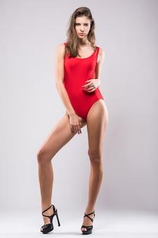 Superbe fille modèle en suite de natation rouge isolé sur fond blanc