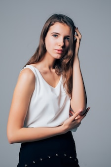 Superbe fille en robe moderne de mode posant en studio isolé sur fond blanc