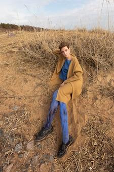 Superbe jeune femme au lookbook automne-hiver de la collection de vêtements pour femmes assise sur le sol dans une élégante robe jaune-bleu.