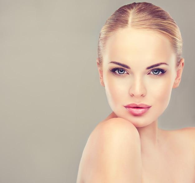 Superbe jeune femme aux cheveux blonds avec une peau fraîche et propre et des cheveux rassemblés dans une coiffure soignée
