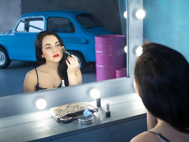 Superbe jeune femme aux cheveux bruns souriante, posant, à l'aide d'un pinceau à maquillage pour appliquer le blush.