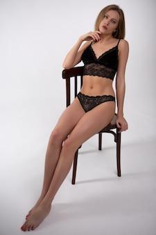 Superbe jeune femme blonde en sous-vêtements en dentelle noire assis sur une chaise en bois