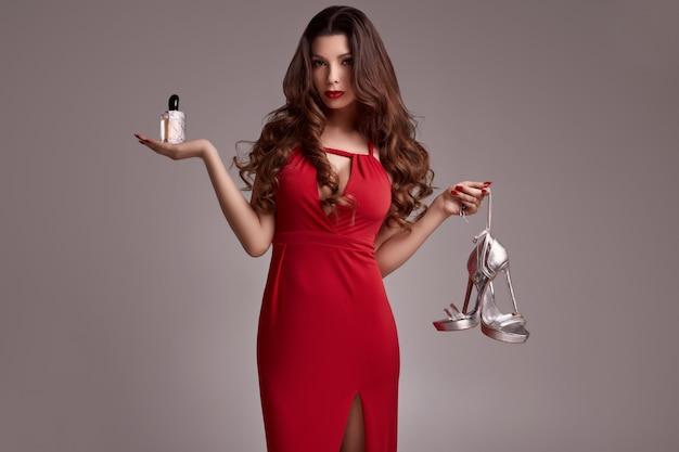 Superbe jeune femme brune aux cheveux bouclés en robe rouge