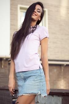 Superbe jeune femme brune posant à l'extérieur par une journée chaude