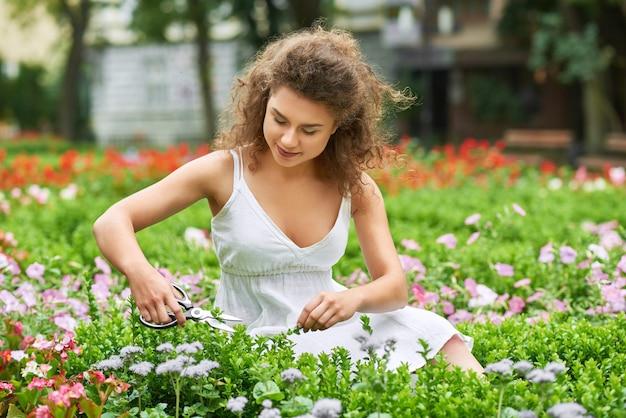 Superbe jeune femme coupant des fleurs dans son jardin, fond, nature, mode de vie, fleuriste, bonheur, passe-temps féminin.
