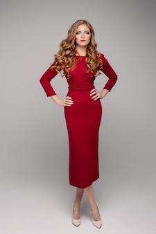 Superbe jeune femme en élégante robe de soirée rouge et talons beiges.