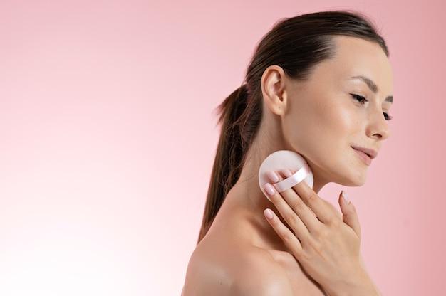 Superbe jeune femme à l'épaule nue utilisant une éponge douce pour appliquer de la poudre sur les joues. modèle féminin caucasien faisant un maquillage léger. isolé sur fond de studio rose.
