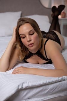 Superbe jeune femme en lingerie de dentelle noire et bas se trouve dans son lit