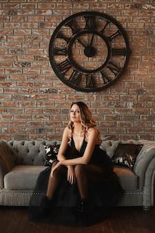 Superbe jeune femme mannequin aux yeux charbonneux dans une belle robe noire avec jupe en tulle est assise sur un canapé