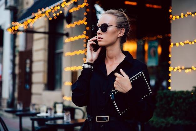 Superbe jeune femme en manteau noir strict parler au téléphone portable, porter des lunettes