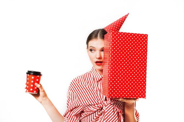 Superbe jeune femme mince portant dans un rouge à rayures avec boîte-cadeau rouge