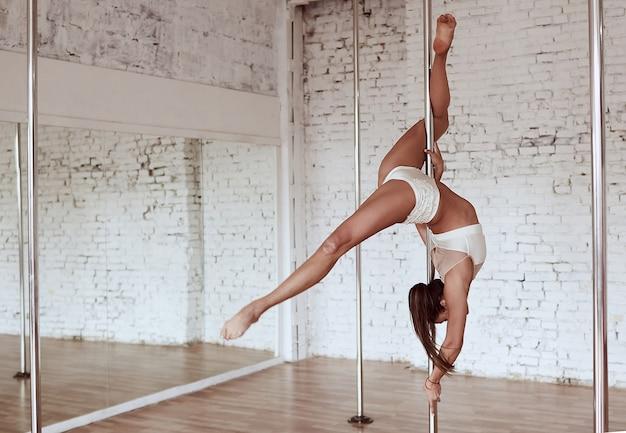 Superbe jeune femme mince en vêtements blancs effectue la pole dance