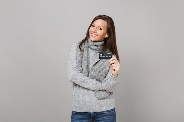 Superbe jeune femme en pull gris, écharpe tenant une carte bancaire de crédit isolée sur fond gris en studio. gens de mode de vie sain émotions sincères, concept de saison froide. maquette de l'espace de copie.