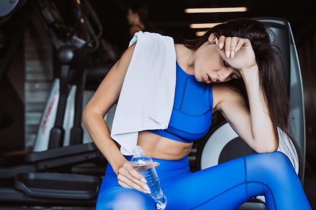 Superbe jeune femme avec une serviette sur son épaule, boire de l'eau provenant d'une bouteille au gymnase