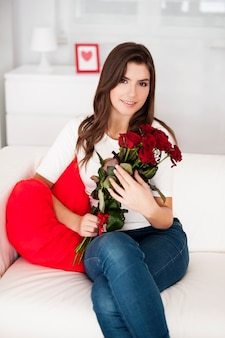 Superbe jeune femme tenant un bouquet de roses rouges
