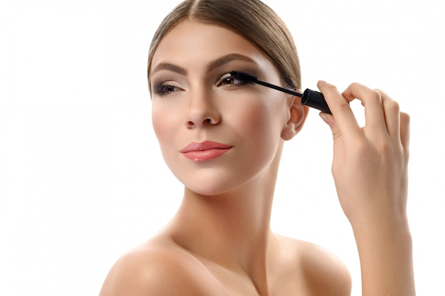 Superbe jeune femme tenant une brosse à mascara isolé sur blanc