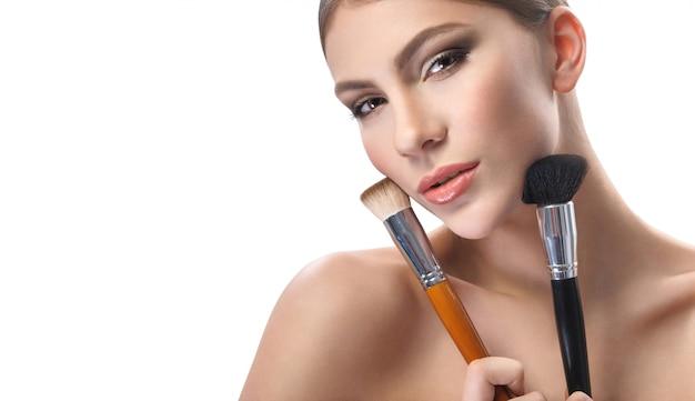 Superbe jeune femme tenant des pinceaux de maquillage isolés sur blanc