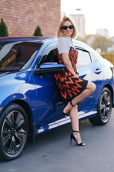 Superbe jeune femme vêtue d'une robe posant devant sa voiture à l'extérieur, conducteur de propriété