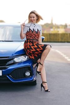 Superbe jeune femme waring dress posant devant sa voiture à l'extérieur, conducteur de propriété