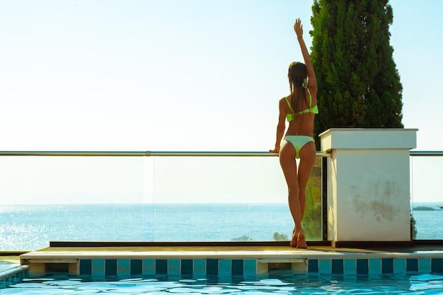 Superbe jeune fille à la piscine posant