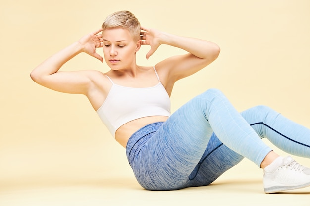 Superbe jeune instructeur de fitness féminin européen avec des cheveux blonds de lutin assis sur le sol avec les mains derrière la tête, montrant la bonne technique de craquements abdiminaux ou d'exercice entrecroisé pour des abdos toniques