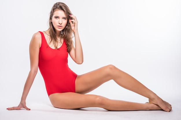 Superbe jeune mannequin aux cheveux brune est assise sur le sol habillé en maillot de bain rouge isolé sur fond blanc